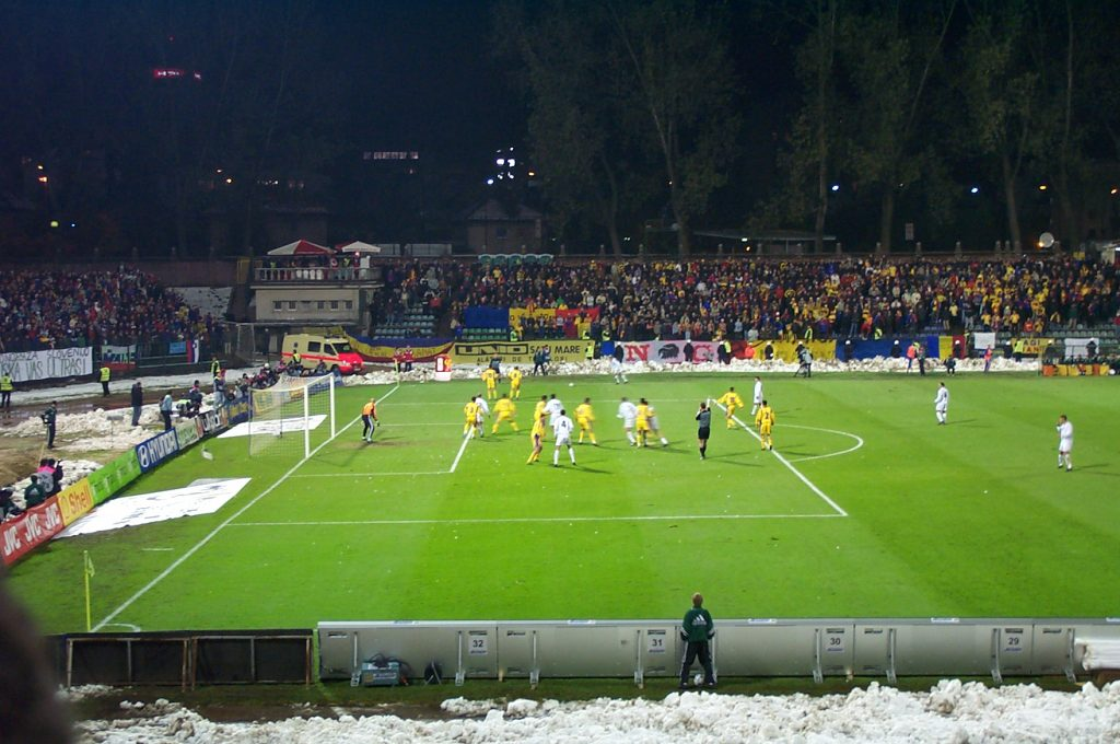 Slovenia (white) takes a free kick while Romania (yellow) defends -- Romania's supporters are at the stadium's far end